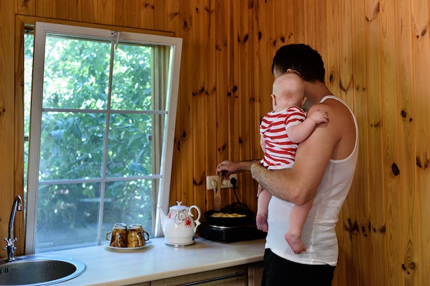 Father with a small baby in his arms is cooking dinner. interior of a country house