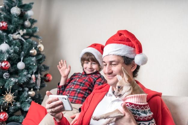 スマートフォンでクリスマスの日にビデオ通話をしている息子と犬を持つ父