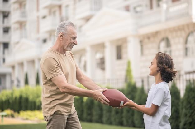 아들과 아버지는 미식 축구를하고 공을 잡고 게임을 시작합니다.