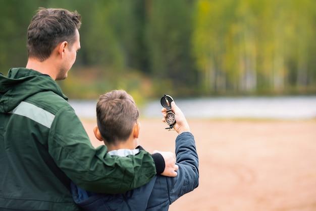 아들과 아버지는 숲에서 나침반을 사용하여 올바른 방법을 찾고 있습니다.