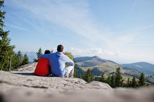 Отец с сыном. дети совершают пешие прогулки в прекрасный день в горах, отдыхают на скалах и любуются прекрасным видом на горные вершины. активный семейный отдых с детьми. веселье на свежем воздухе и полезные для здоровья занятия.