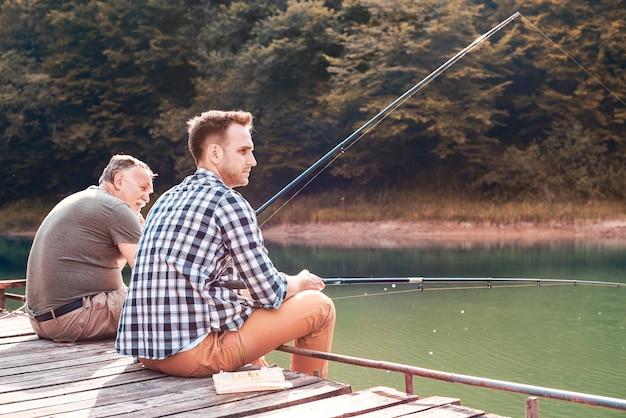 桟橋で釣りをしている息子を持つ父