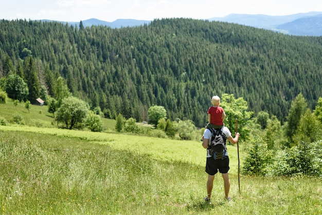Father with son on his shoulders standing with staff in green forest, mountains and sky with clouds. back view