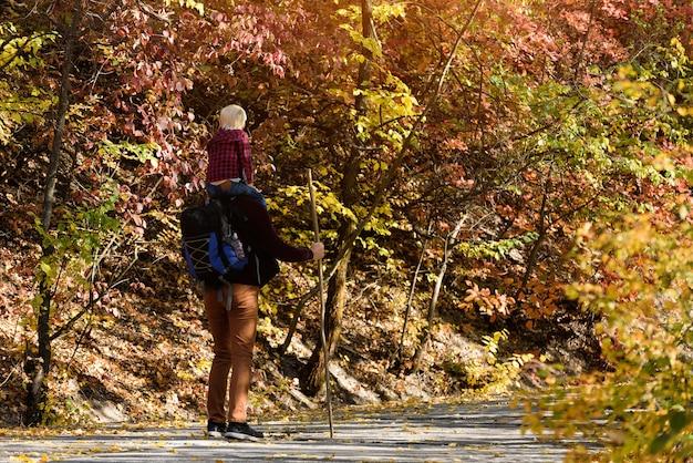 秋の公園を歩いている彼の肩に息子を持つ父。晴れた日。背面図
