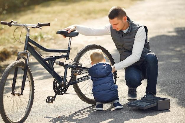 Il padre con il figlio ripara la bici in un parco