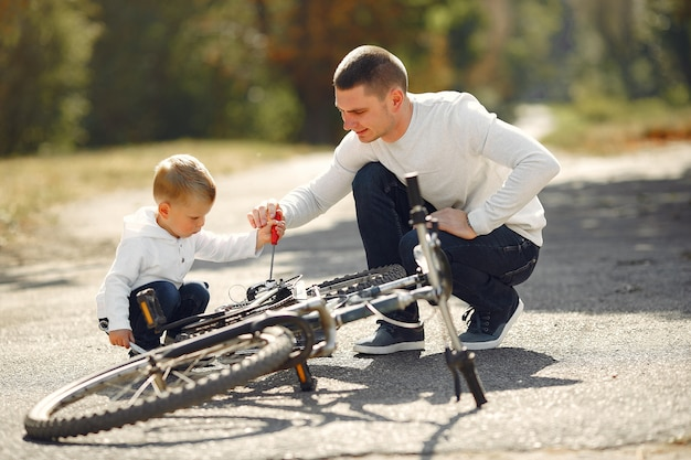 Father with son repare the bike in a park