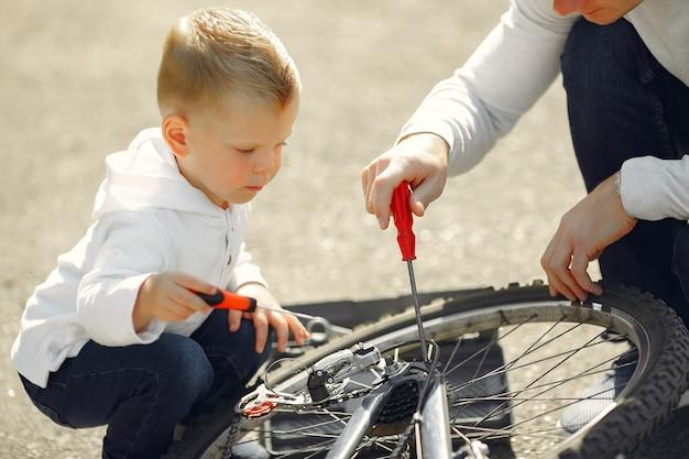 Отец с сыном ремонтируют велосипед в парке