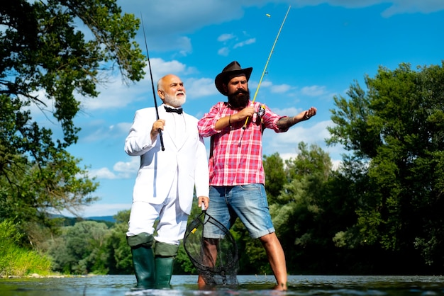 Father with son on the river enjoying fishing holding fishing rods portrait of cheerful two bearded ...