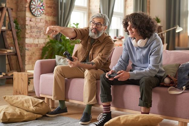自宅の居間で遊んでいる間、ソファに座って彼らのゲームについて話し合う息子を持つ父