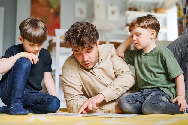 Отец с сыновьями читают книгу, проводят время вместе дома и лежа на полу