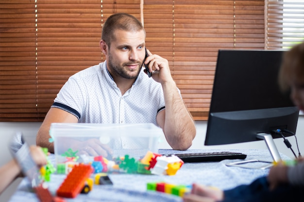 무릎에 두 명의 작은 소년이있는 아버지는 집에서 웃으려고합니다. 젊은 남자가 아이를 돌보아 컴퓨터에서 작동합니다.