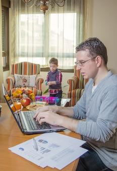 Отец работает в домашнем офисе и сын играет