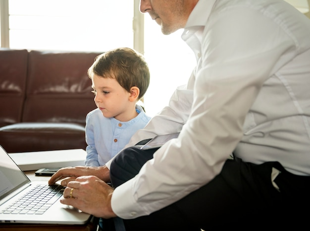 Father working on laptop next to son