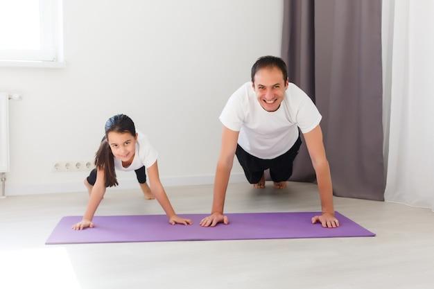 Отец тренируется, делает планку на одной руке со своей дочерью. дома квартира.