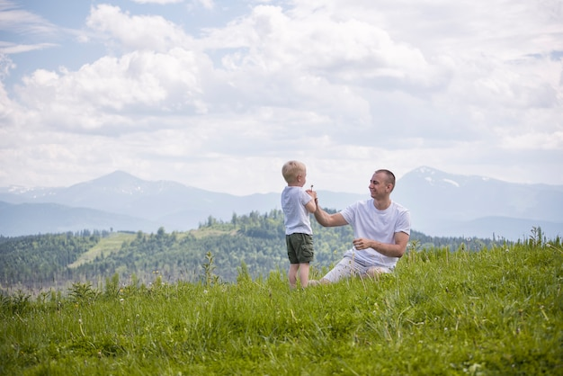 Father and young son are blowing dandelions sitting in the grass on a  of green forest, mountains and sky with clouds. friendship