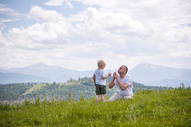 Father and young son are blowing dandelions sitting in the grass, mountains and sky with clouds. friendship concept