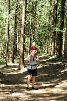 Father and young son on his shoulders walking on a coniferous forest