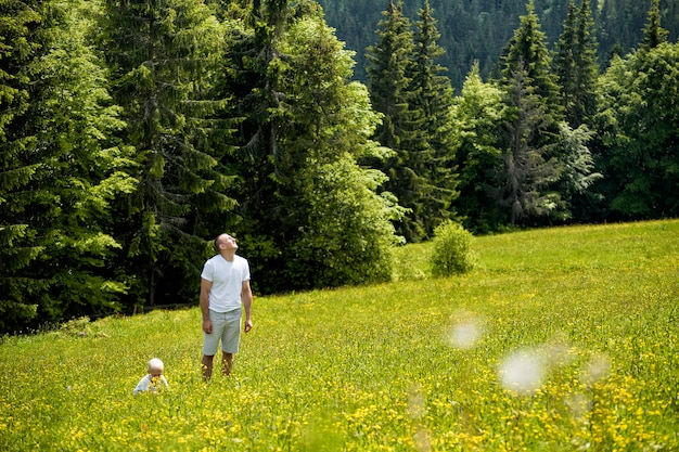 Father and young son walking on a green meadow, green pine forests.