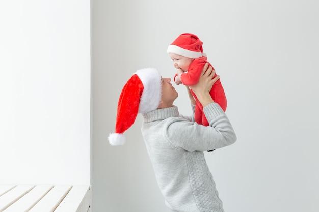 Концепция отцовства и праздников - отец со своим мальчиком в шляпах санта-клауса празднует рождество