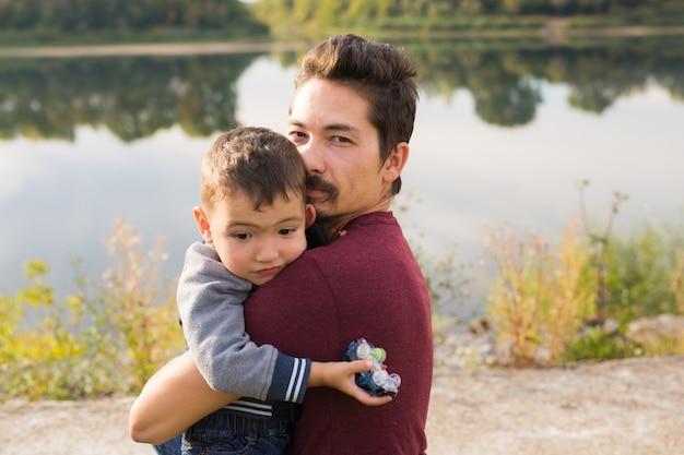 Концепция отцовства, семьи и отцовства - отец держит своего маленького сына