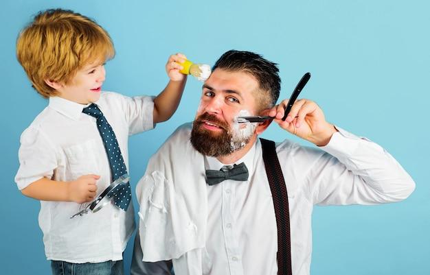 아버지의 날. 아빠의 어시스턴트. 수염을 면도하는 아들과 아빠. 수염 관리. 작은 이발사. 이발소 개념입니다.