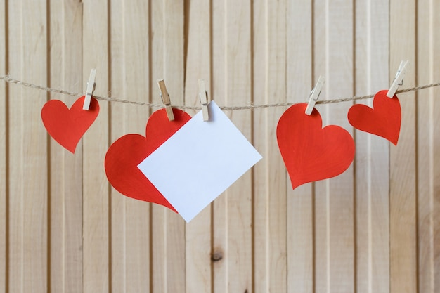 Fathers day. card for message with paper hearts hanging with clothespins over light wooden board. birthday. valentines day. wedding