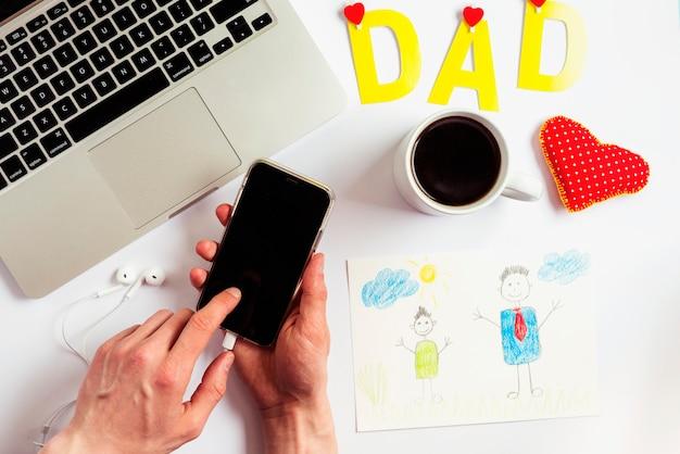 Composizione di giorno di padri con laptop e smartphone