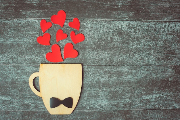 Fathers day concept. decorative cup with bow-tie and hearts. copyspace.