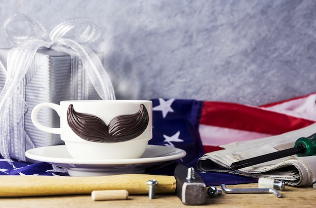 Fathers day concept of hot coffee with mustache and tool on the table and american flag