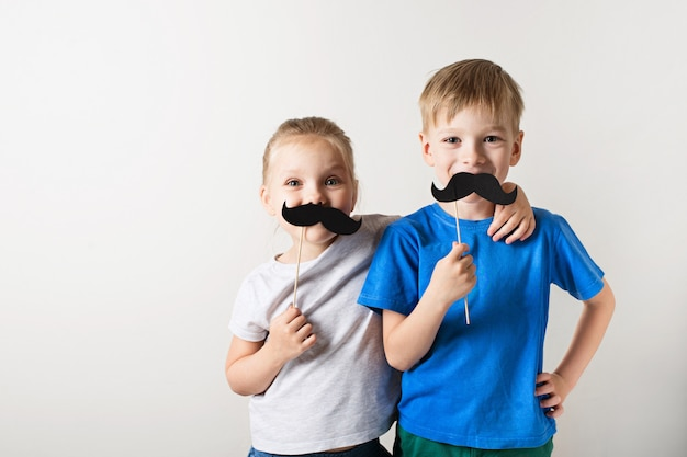 Fathers day concept, two little caucasian kids smiling with moustache on white background