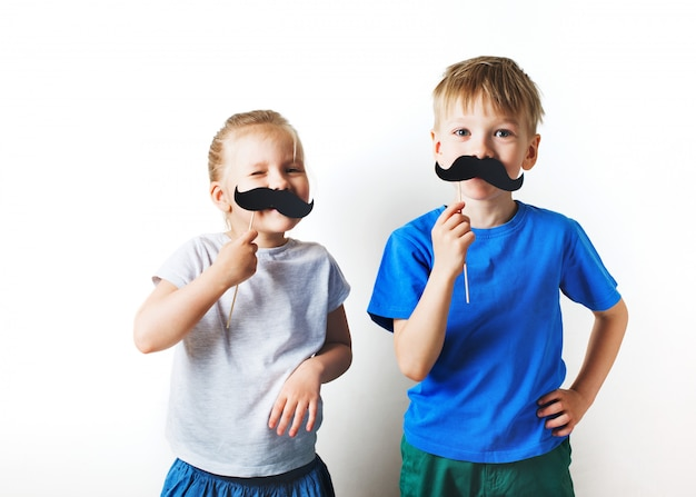 Fathers day concept, two little caucasian kids with moustache on white background