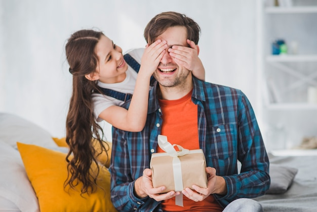 Fathers day concept with daughter covering fathers eyes