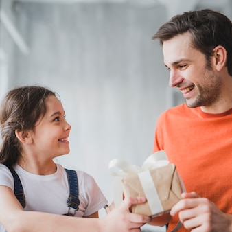 Fathers day concept with daughter giving present