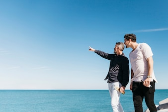 Fathers day concept with father and son pointing towards sea
