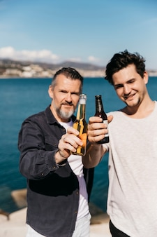 Fathers day concept with father and son showing beer