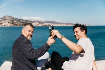 Fathers day concept with father and son toasting with beer at sea