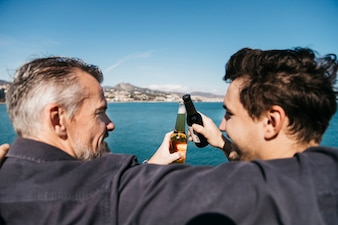 Fathers day concept with father and son toasting with beer in front of water