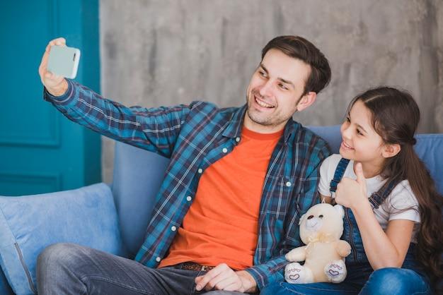 Concetto di giorno di padri con padre e figlia prendendo selfie