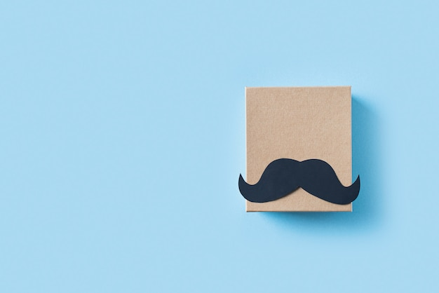 Fathers day concept with gift  box and mustache on blue background
