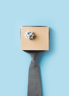Fathers day concept with gift  box and tie on blue background