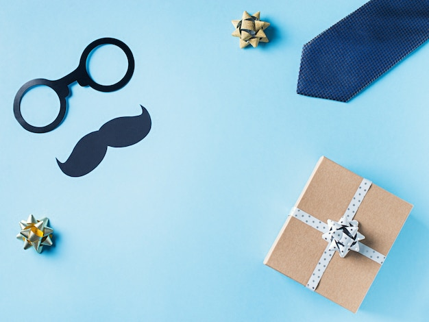 Fathers day concept with gift  box, tie and mustache on blue background