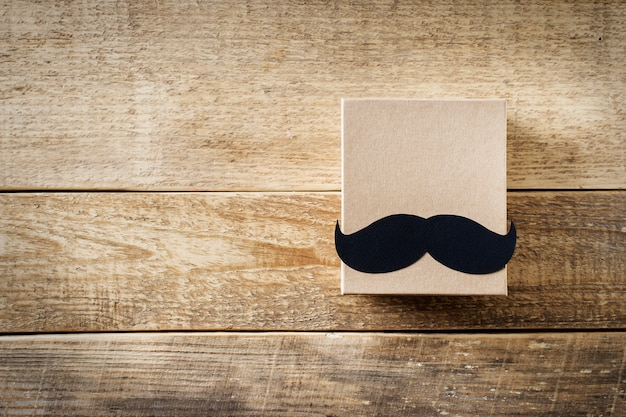 Fathers day concept with mustache and gift box on wooden background