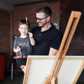 Fathers day concept with smiling father and son in front of canvas