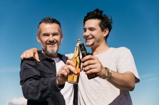 Concetto di giorno di padri con padre e figlio sorridenti che tostano con la birra