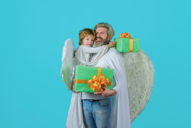 Подарочная коробка ко дню отца маленький мальчик-купидон дарит отцу подарок счастливый отец в костюме ангела с маленьким