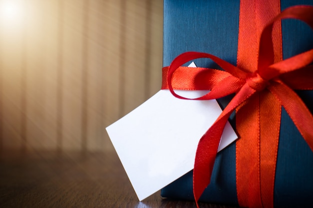 Fathers day. gift package wrapped with blue paper and rope with a red ribbon on wooden background. copyspace