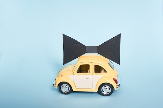 Fathers day greeting card with yellow toy car and black paper tie on blue background