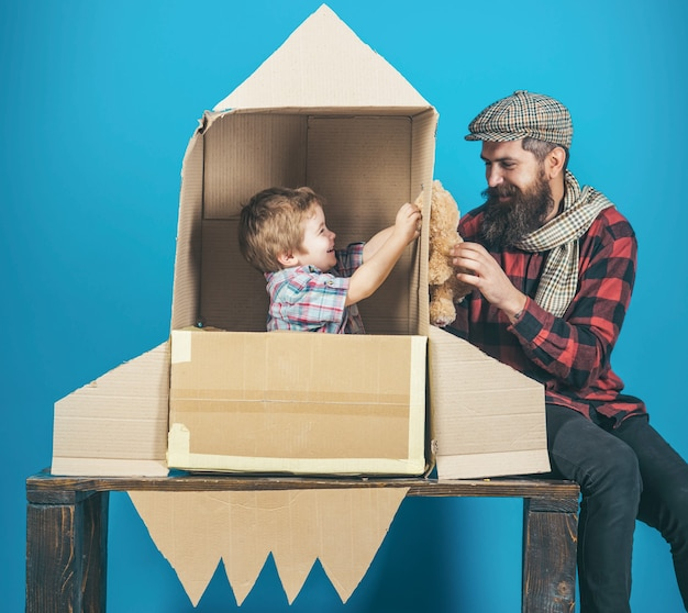 Fathers day happy family playing with cardboard rocket cosmonaut concept cute boy playing cosmonaut