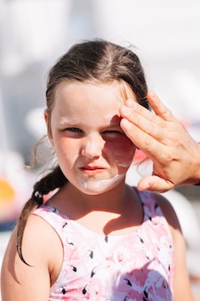 The fathers hand applies sunscreen from burns and ultraviolet light on the daughters face on a hot s...