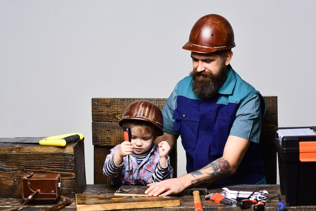 Fatherson in workshop repairing father teaching little son to repair fatherhoodtransfer of